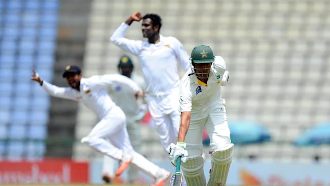 Pakistan's Younis Khan (R) is run out as Sri Lankan cricketers celebrate during the second day of the third and final Test in Pallekele on July 4, 2015