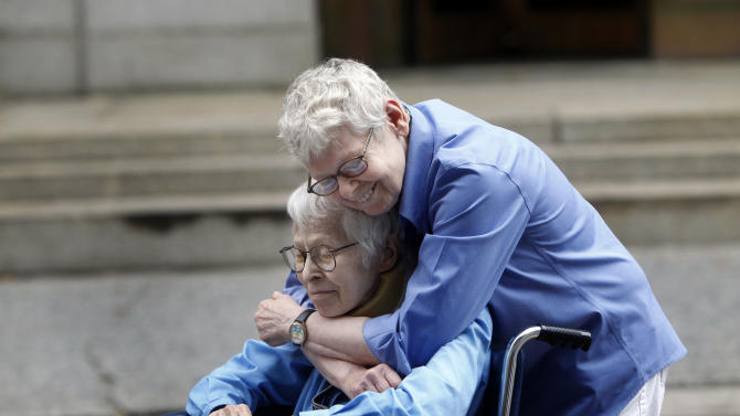 CORRECTS POSITIONS OF SUBJECTS - Phyllis Siegel, 77, right, and Connie Kopelov, 85, both of New York, embrace after becoming the first same-sex couple to get married at the Manhattan City Clerk's office, Sunday, July 24, 2011, in New York. (AP Photo/Jason DeCrow)