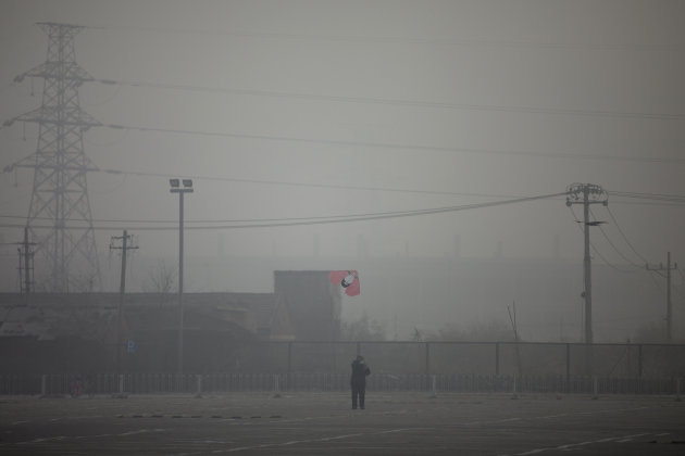 A man flies a kite near electricity pylons on a hazy day in Beijing Saturday, Jan. 12, 2013. Air pollution levels in China&#39;s notoriously dirty capital were at dangerous levels Saturday, with cloudy skies blocking out visibility and warnings issued for people to remain indoors. (AP Photo/Alexander F. Yuan)