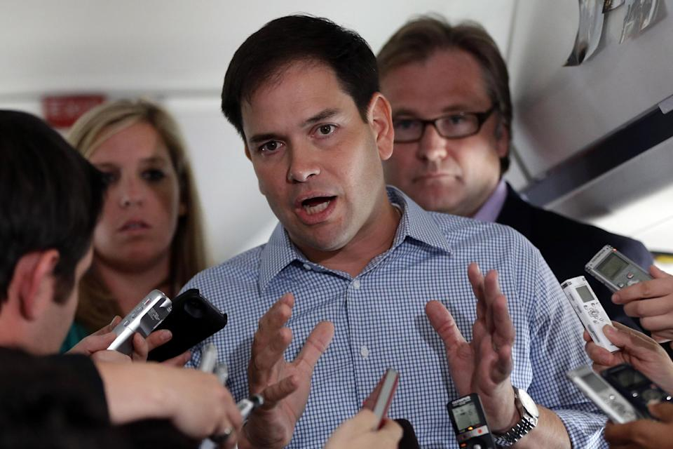 Sen. Marco Rubio, R-Fla., who is traveling with Republican presidential candidate and former Massachusetts Gov. Mitt Romney, speaks to reporters on his campaign plane en route to Orlando, Fla., Saturday, Oct. 27, 2012. At rear right is senior adviser Eric Fehrnstrom. (AP Photo/Charles Dharapak)