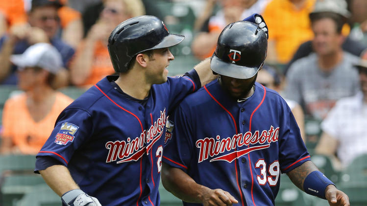 Minnesota Twins' Brian Dozier, left, celebrates with teammate Danny Santana after scoring on Joe Mauer's triple in the sixth inning of a baseball game against the Baltimore Orioles, Monday, Sept. 1, 2014, in Baltimore. (AP Photo/Patrick Semansky)