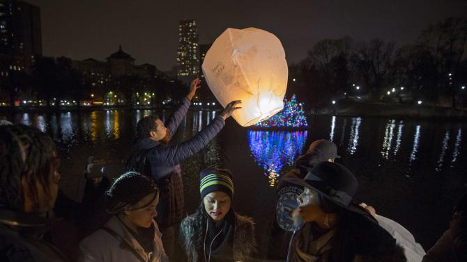 A man releases a sky lantern as demonstrators gather in Central Park in Harlem