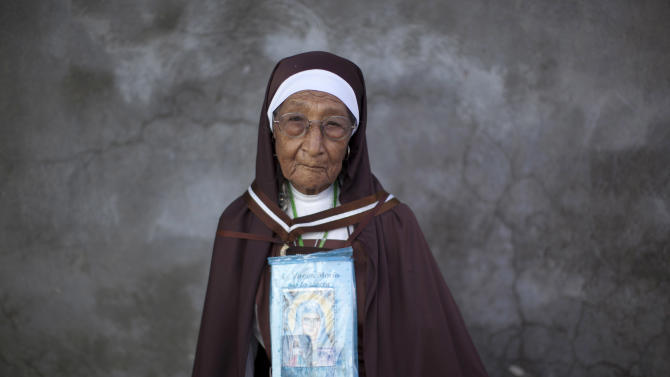 In this Aug. 26, 2012, Catholic nun Maria Reyes, from the Carmelitas del Purgatorio order, who is a follower of Our Lady of the Rosary religious sect, wears an image of the Virgin Mary in Nueva Jerusalen, Mexico.  Sect members say Our Lady of the Rosary left instructions for followers on how to live, including no public education, which is at the heart of a confrontation brewing at the complex among the sect's traditionalists, its more reformist members and the Mexican government.  (AP Photo/Alexandre Meneghini)