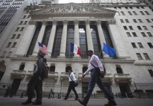People walk past the New York Stock Exchange as it flies the U.S., French and Eurozone flags in New York