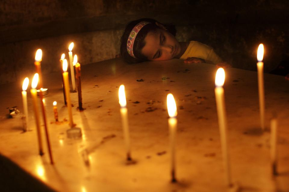 A Catholic worshipper pauses after participating in Good Friday processions inside the Church of the Holy Sepulchre, traditionally believed to be the burial site of Jesus Christ, Friday, April 6, 2012. (AP Photo/Bernat Armangue)
