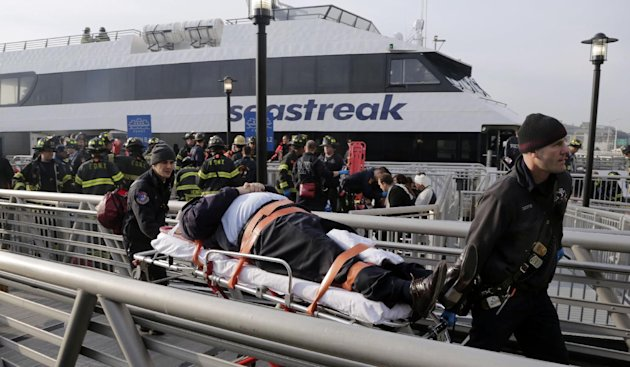 An injured passenger from the Seastreak Wall Street ferry is taken to an ambulance, in New York, Wednesday, Jan. 9, 2013. The ferry from Atlantic Highlands, N.J., banged into the mooring as it arrived at South Street in lower Manhattan during morning rush hour, injuring as many as 50 people, at least one critically, officials said.(AP Photo/Richard Drew)