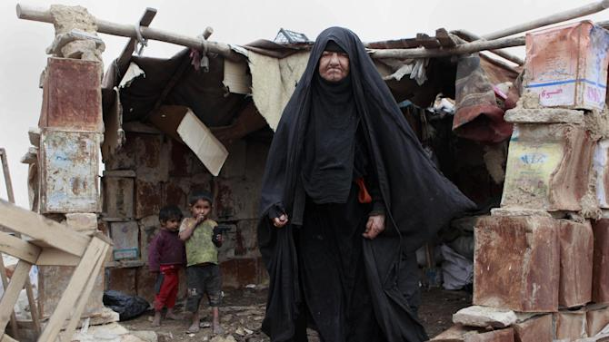Umm Jassim stands with her grandsons in the wreckage of their home, destroyed after heavy rain, at a compound for displaced people in Baghdad's southeastern Zaafaraniyah district, Wednesday, Feb. 6, 2013. An estimated 1.55 million people are currently displaced inside Iraq due to sectarian violence that threatened their lives. (AP Photo/ Hadi Mizban)