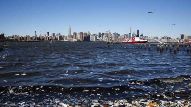 Charred documents wash up near where members of the New York Fire Department battled a six alarm fire in a storage facility on the waterfront of the East River in New York