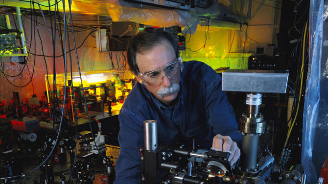 "In this 2003 photo provided by Geoffrey Wheeler and the National Institute of Standards and Technology, physicist David Wineland adjusts an ultraviolet laser beam used to manipulate ions in a high-vacuum apparatus containing an ""ion trap"" used to demonstrate the basic operations required for a quantum computer. Wineland and Serge Haroche of France shared the 2012 Nobel Prize in physics Tuesday, Oct. 9, 2012 for inventing methods to observe the bizarre properties of the quantum world, research that has led to the construction of extremely precise clocks and helped scientists take the first steps toward building superfast computers. (AP Photo/NIST, Geoffrey Wheeler)"