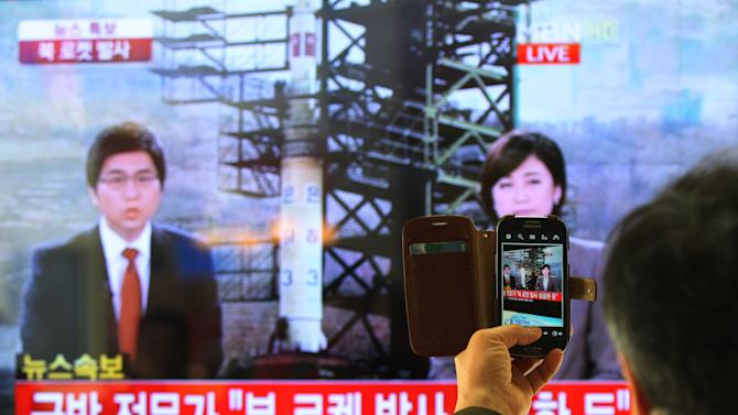 """FILE - In this Dec. 12, 2012 file photo, a South Korean man uses his smartphone to take a photo of a television screen reporting a news about North Korea's rocket launch with a banner reading: """"North Korea's rocket launch seems to be successful"""" at Seoul Railway Station in Seoul, South Korea. After three nuclear tests of apparently increasing power and a long-range rocket launch that puts it a big step closer to having a missile that can carry a nuclear warhead to American shores, many believe that, in a matter of years - as little as five, maybe, though the timeframe is a point of debate - Pyongyang will have a very scary nuclear arsenal. Though it's a view not embraced by everyone, one respected South Korean expert says North Korea could be working toward 80 to 100 nuclear-tipped missiles. (AP Photo/Ahn Young-joon, File)"""