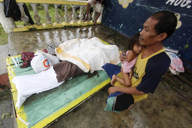 A resident cuddles his child next to the bodies of three children who were killed in a landslide that swept their home after Typhoon Bopha made a landfall in Compostela Valley in southeastern Philippines Tuesday, Dec. 4, 2012. Typhoon Bopha , one of the strongest typhoons to hit the Philippines this year, barreled across the country's south on Tuesday, killing dozens of people and forcing more than 50,000 to flee from inundated villages. (AP Photo/Karlos Manlupig)
