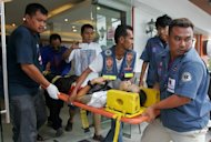 Rescuers carry out a man injured in a bombing in Thailand&#39;s Pattani town today. A series of blasts shook a town in the restive Thai south leaving three dead and 17 wounded, officials said today, days after a major attack on a military base in the unrest-hit region
