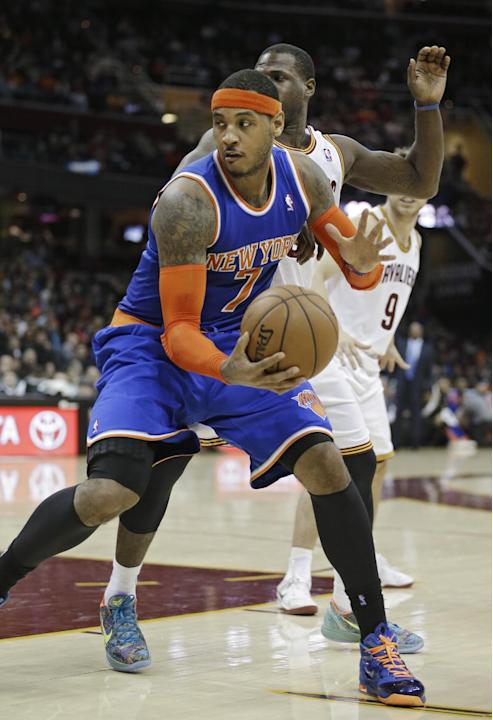 New York Knicks' Carmelo Anthony (7) spins inside Cleveland Cavaliers' Dion Waiters in the fourth quarter of an NBA basketball game Tuesday, Dec. 10, 2013, in Cleveland