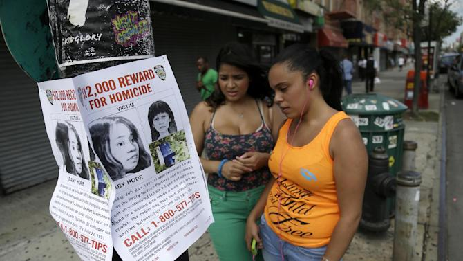 """In this Tuesday, July 23, 2013, photo passersby look at a poster soliciting information regarding an unidentified body near the site where the body was found in New York. More than two decades after the body of a child was found inside a cooler, the New York Police Department is seeking help identifying the girl dubbed """"Baby Hope."""" On Tuesday, the 22nd anniversary of the discovery, police offered a $12,000 reward for any information leading to an arrest and conviction in the unsolved crime. (AP Photo/Seth Wenig)"""