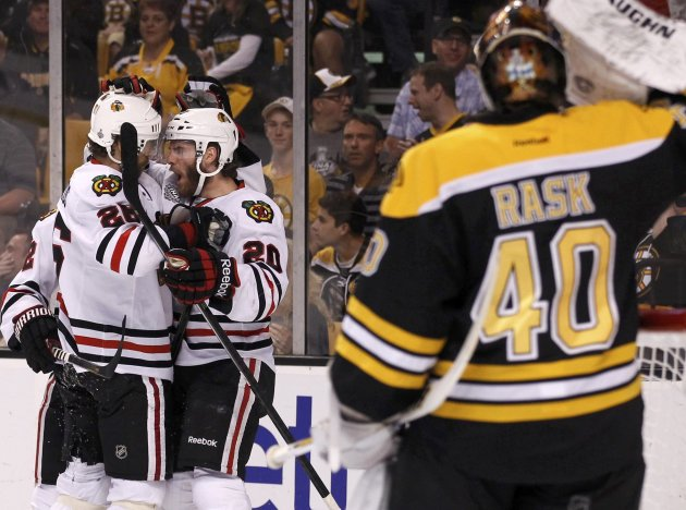 Blackhawks' Handzus celebrates his first period goal with teammate Saad as Bruins goalie Rask takes a drink during Game 4 of their NHL Stanley Cup Finals hockey series in Boston