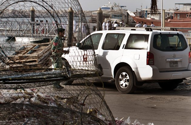 Emirati police and other officials inspect a boat docked in a fishing harbor in the Jumeirah district of Dubai, United Arab Emirates, Monday, July 16, 2012. A U.S. official in Dubai says an American vessel has fired on a boat off the coast of the United Arab Emirates, killing one person and injuring three. The official gave no further details, but it appears the boat could have been mistaken as a threat in Gulf waters not far from Iran's maritime boundaries. (AP Photo/Almoutasim Almaskery)