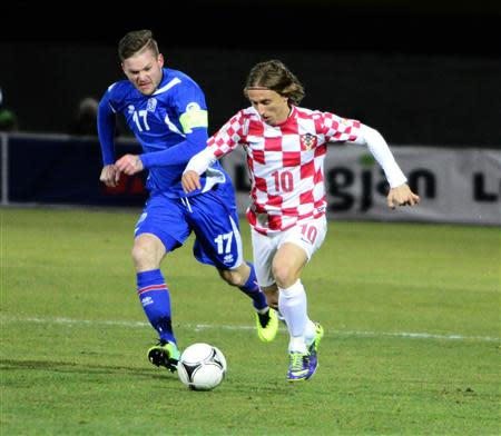 Modric of Croatia challenges Gunnarsson of Iceland during their 2014 World Cup playoff soccer match in Reyjkavik