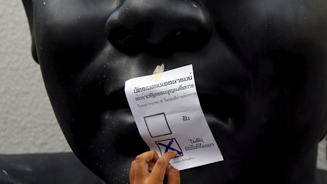 "An opposition student attaches a mock ballot with the option ""No"" seletcted to an statue during a protest against the military-backed draft constitution in Bangkok"
