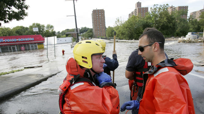 Paterson firefighters suite up for a possible rescue on Bridge Street as the swollen Passaic River floods Paterson, N.J., Wednesday, Aug. 31, 2011. (AP Photo/Rich Schultz)