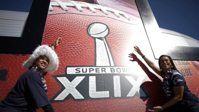 New England Patriots fans pose for a picture outside of the stadium ahead of the start of the NFL Super Bowl XLIX football game against the Seattle Seahawks in Glendale