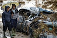 Residents walk by wrecked cars carried away by flash floods after heavy rain in the town of Villanueva del Rosario, Malaga, southern Spain, Friday, Sept. 28, 2012. Homes were destroyed and at least one woman was killed. Rescue workers are searching to determine if there are more victims. (AP Photo/Sergio Torres)