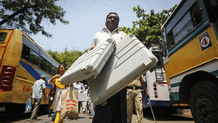 A member of election staff carries electronic voting machines from distribution centre ahead of sixth phase of India's general election in Mumbai