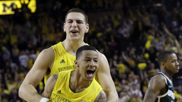 Michigan guard Trey Burke, foreground, and teammate forward Mitch McGary celebrate their 58-57 win over Michigan State in an NCAA college basketball game in Ann Arbor, Mich., Sunday, March 3, 2013. (AP Photo/Carlos Osorio)