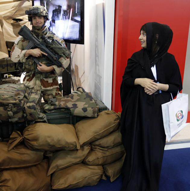 An Emirati woman looks over at a French soldier during the launching of the International Defence Exhibition and Conference (IDEX) at the Abu Dhabi National Exhibition Centre in the Emirati capital on