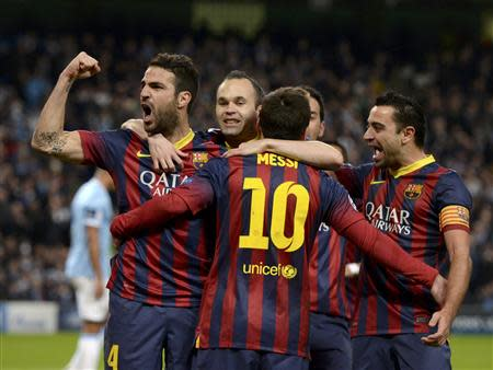 Barcelona players celebrate Lionel Messi's penalty against Manchester City during their Champions League round of 16 first leg soccer match at the Etihad Stadium in Manchester