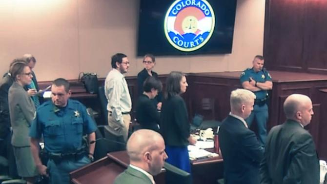 In this image made from Colorado Judicial Department video, James Holmes, background fifth from left in white shirt, stands along with others as the jury enters the courtroom, during the sentencing phase of the Colorado theater shooting trial in Centennial, Colo., on Wednesday, July 29, 2015. (Colorado Judicial Department via AP, Pool)