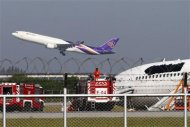 Airport staff works around a Thai Airways plane that skidded off the runaway while landing, as another takes off in the distance, at Bangkok's Suvarnabhumi Airport September 9, 2013. REUTERS/Athit Perawongmetha