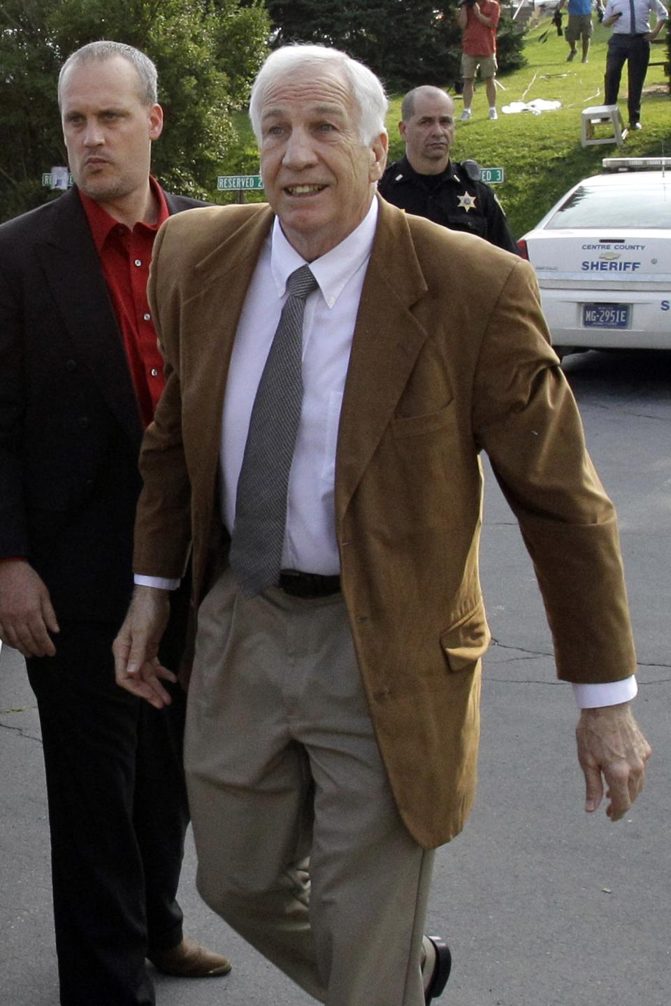 Former Penn State University assistant football coach Jerry Sandusky, center, arrives at the Centre County Courthouse in Bellefonte, Pa., Friday, June 22, 2012. Sandusky is accused of sexual abuse of 10 boys over a 15-year period.   (AP Photo/Gene J. Puskar)