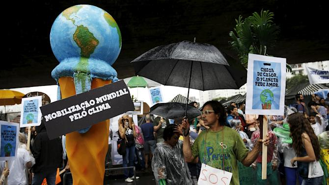 Sign of a melting ice cream in the form of the planet is seen next to activists during a rally held the day before the start of the Paris Climate Change Conference (COP21), in Sao Paulo
