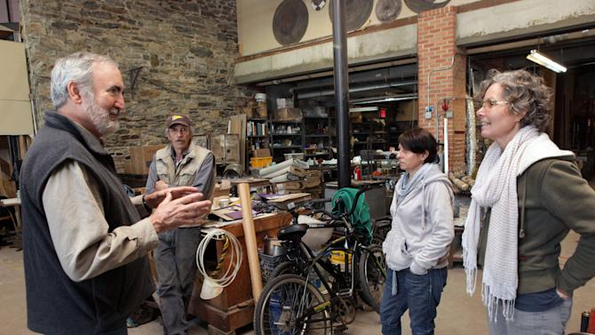 This Dec. 3, 2012, photo provided by Craft Emergency Relief Fund  (CERF+) Craig Nutt,far  left, of CERF+ talks to three artists at Pier Glass in the Red Hook neighborhood of Brooklyn, New York, from left, Kevin Kutch, Alison Ruzsa and Mary Ellen Buxton-Kutch.  Pier Glass received a $3,000 grant from CERF. After beig nundated with salt water from Superstorm Sandy, the studio estimates the damage at up to $200,000. They received a $3,000 grant from CERF+.   (AP Photo/CERF+, George Hirose)