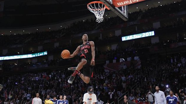 East All-Star Terrence Ross of the Toronto Raptors jumps over a boy as he competes in the slam dunk contest during the NBA basketball All-Star weekend in Houston, Texas, February 16, 2013 (Reuters)
