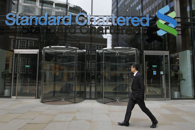 A man walks by the headquarter of Standard Chartered bank in the City of London, Tuesday, Aug. 7, 2012. Shares in Standard Chartered PLC dropped sharply on Tuesday as investors reacted to U.S. charges