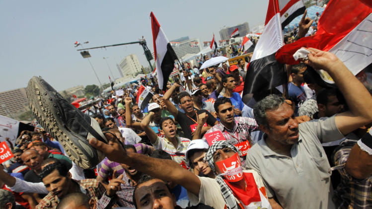 """Opponents of Egypt's Islamist President Mohammed Morsi shout slogans during a protest in Tahrir Square in Cairo, Egypt, Wednesday, July 3, 2013. A Defense Ministry official said army chief Gen. Abdel-Fattah el-Sissi is meeting with his top commanders, hours before the military's deadline to the president and opposition to resolve the nation's political crisis is set to expire. Arabic reads, """"Leave."""" (AP Photo/Amr Nabil)"""
