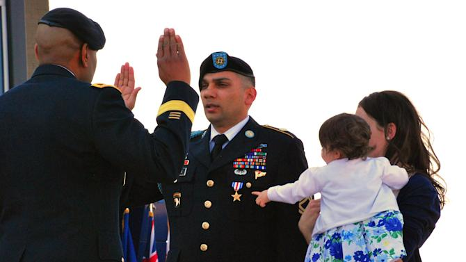 CORRECTS RANK TO SGT. 1ST CLASS INSTEAD OF STAFF SGT. - Sgt. 1st Class  Matthew Loheide re-enlists in the Army on Friday, April 5, 2013, at Fort Campbell, Ky., while his daughter, Annabella, held by Marianne Loheide, points to his Silver Star. Loheide received the Silver Star for his actions to evacuate wounded soldiers while in Afghanistan in 2010. (AP Photo/Kristin M. Hall)