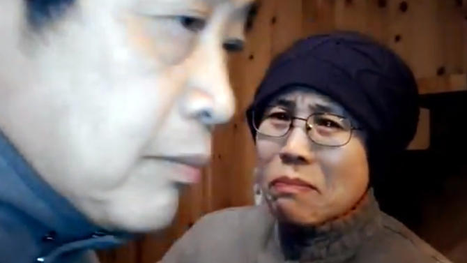 FILE - In this Dec. 28, 2012 file image made from a video and provided by Hu Jia via AP Video, Liu Xia, right, wife of 2010 Nobel Peace Prize winner Liu Xiaobo, reacts to an unexpected visit by a group of activists at her home in Beijing, China. Chinese activists are urging the public to visit dissident Liu's wife to highlight that she has been under house arrest since her husband won the Nobel Peace Prize in 2010. The person at left is Beijing intellectual Xu Youyu. (AP Photo/Hu Jia via AP Video) EDITORIAL USE ONLY