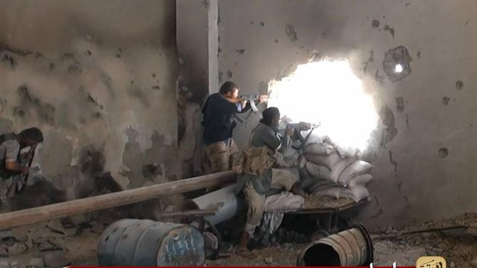 An image obtained from jihadist media outlet Welayat Raqa on July 25, 2014 allegedly shows Islamic State (IS) members firing towards Syrian forces in the rebel-held Syrian city of Raqa