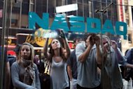 People look into the window of the Nasdaq stock market moments before Facebook shares went public May 18, in New York. Facebook stumbled on its first trading day as shares ended barely above the starting price, raising questions about what will happen to the share price when the Nasdaq reopens on Monday