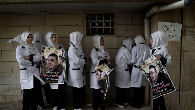 "Palestinian nurses hold posters with the picture of Maysara Abu Hamdiyeh with Arabic that reads, ""captive martyr brigade, Maysara Abu Hamdiyeh, the captive movement martyr, died on April 2, 2013,"" outside the morgue of a hospital in the West Bank city of Hebron, Thursday, April 4, 2013. Demonstrations first erupted across the West Bank on Tuesday over the death of a Palestinian prisoner who died from cancer. The  64-year-old prisoner, Hamdiyeh, was serving a life sentence for a 2002 foiled bombing of a busy Jerusalem cafe. After Abu Hamdiyeh died, the Palestinians blamed Israel for the death, saying he was not given proper medical care. Israel says the prisoner was treated by specialist doctors in hospital.(AP Photo/Bernat Armangue)"