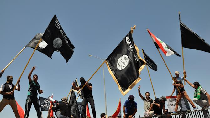 Masked Sunni protesters wave Islamist flags while others chant slogans at an anti-government rally in Fallujah, Iraq, Friday, April 26, 2013.  Iraqi soldiers backed by tanks retook control of a Sunni town north of Baghdad on Friday after gunmen withdrew without a fight, although violence continued in other parts of the country. The Sunni gunmen had seized Suleiman Beg on Thursday after a firefight with security forces, one in a string of similar incidents that have killed more than 150 people in clashes in Sunni Muslim towns in western and northern Iraq over the past four days.(AP Photo/Bilal Fawzi)
