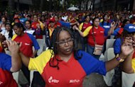Supporters of Venezuelan President Hugo Chavez pray during a mass in the center of Caracas, on December 11, 2012. Chavez is now recovering after a successful cancer operation at a Cuban hospital, according to his vice president