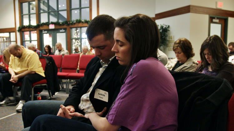"In this Dec. 23, 2012 photo, three weeks back home from the war in Afghanistan, U.S. Army 1st Lt. Aaron Dunn and his wife Leanne pray during services at their church, in Colorado Springs, Colo. On war and coming home, Dunn says: ""War and coming home are going to mean different things to each soldier. For me it was God and Family. I get my security in life from my hope in God, and my companionship and support from my family."" (AP Photo/Brennan Linsley)"