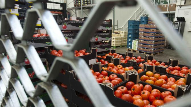 Boxes containing  tomatoes stand behind a fence at the closed shop of a distributor at the central fruit and vegetable market in Berlin on Tuesday, afternoon, May 31, 2011. The selling of vegetables especially tomatoes, cucumbers and salad went down after the products are suspected to cause the E. coli outbreak in Germany. (AP Photo/Markus Schreiber)