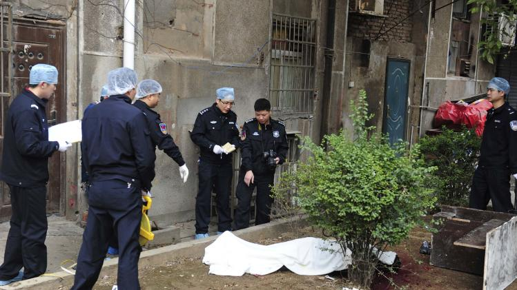 Investigators look at a covered body lying on the ground at a crime scene on a street in Changsha