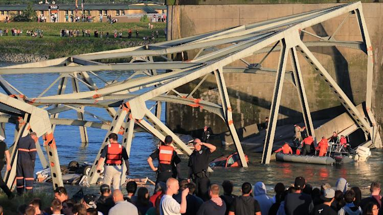 In this photo provided by Francisco Rodriguez, rescue workers surround the scene where a pickup truck and a car fell into the Skagit River after the collapse of the Interstate 5 bridgeThursday, May 23, 2013, in Mount Vernon, Wash. (AP Photo/Francisco Rodriguez)