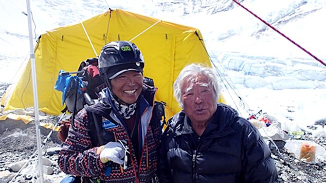 In this Saturday, May 18, 2013 photo distributed by Miura Dolphins, 80-year-old Japanese adventurer Yuichiro Miura, right, is greeted by his friend climber Kenji Kondo while resting at his camp at 6,500 meters (21,325 feet) during his attempt to scale the summit of Mount Everest. According to his management office, Miura plans to accomplish the ascent on Thursday, May 23 to be the world's oldest person to reach the world's highest peak. (AP Photo/Miura Dolphins)  MANDATORY CREDIT