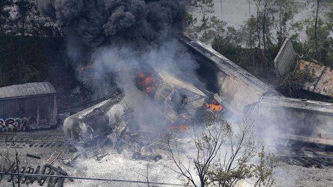 A fire burns at the site of a CSX freight train derailment, Tuesday, May 28, 2013, in White Marsh, Md., where fire officials say the train crashed into a trash truck, causing an explosion that rattled homes at least a half-mile away and collapsed nearby buildings, setting them on fire. (AP Photo/Patrick Semansky)